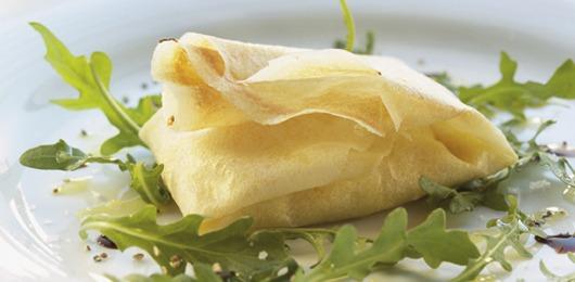 Pastelão de queijo cabra sobre salada morna de rúcula e tomate cereja